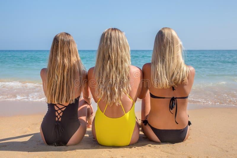 Três meninas holandesas louras sentam-se na praia imagens de stock