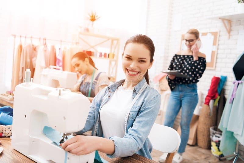 Três meninas na fábrica do vestuário Estão sentando-se atrás das máquinas de costura foto de stock royalty free