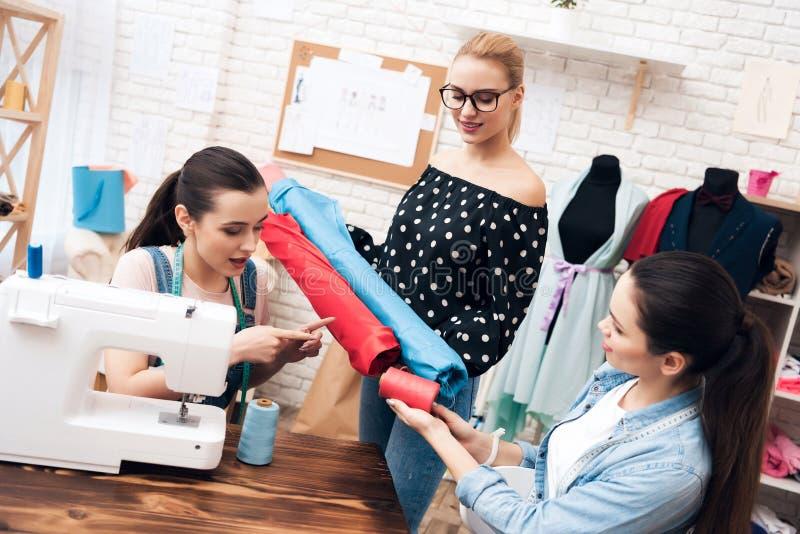 Três meninas na fábrica do vestuário Estão sentando-se atrás das máquinas de costura e estão escolhendo-se a tela para o vestido  imagens de stock