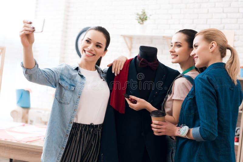Três meninas na fábrica do vestuário Estão tomando o selfie com o revestimento novo do terno fotos de stock royalty free