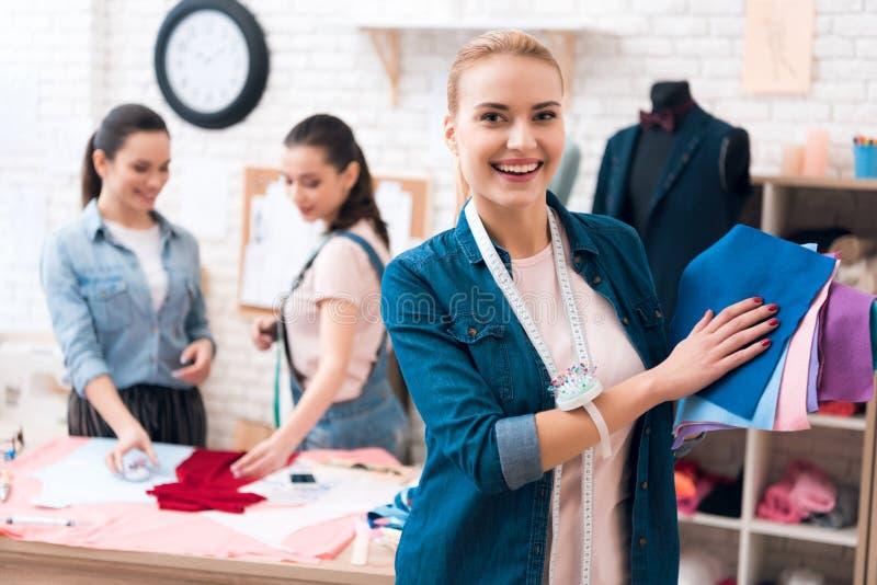 Três meninas na fábrica do vestuário Um deles está levantando no primeiro plano com tela para o vestido novo imagens de stock royalty free