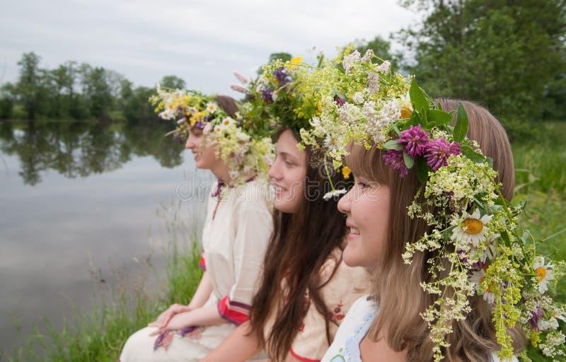 Três meninas no chaplet da flor imagem de stock
