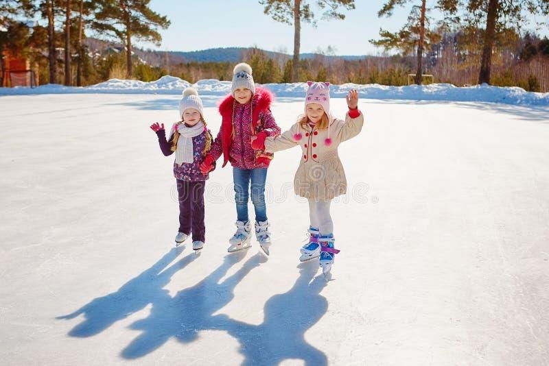 Três meninas patinam no gelo Férias e feriados em n fotografia de stock royalty free