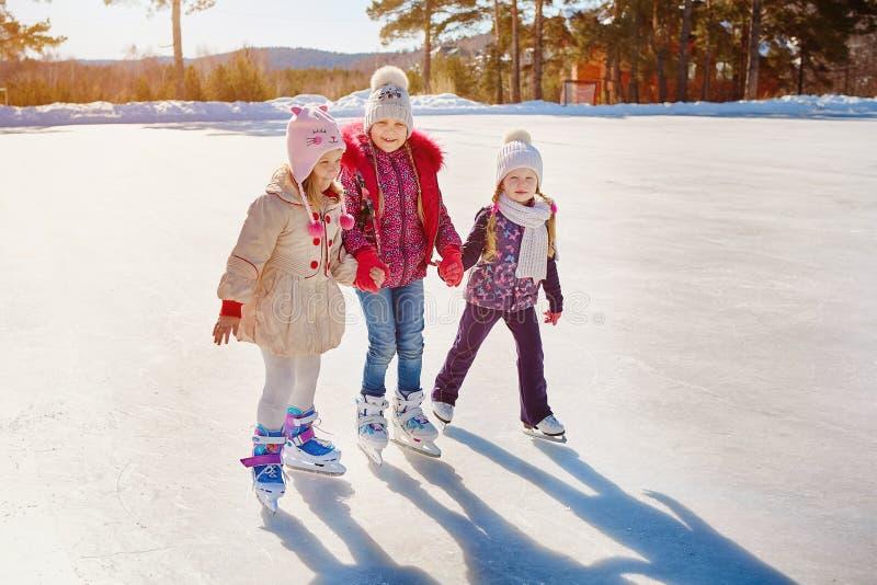 Três meninas patinam no gelo Férias e feriados na natureza fotografia de stock royalty free
