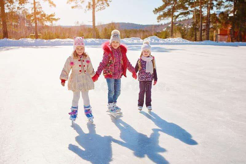 Três meninas patinam no gelo Férias e feriados na natureza imagem de stock