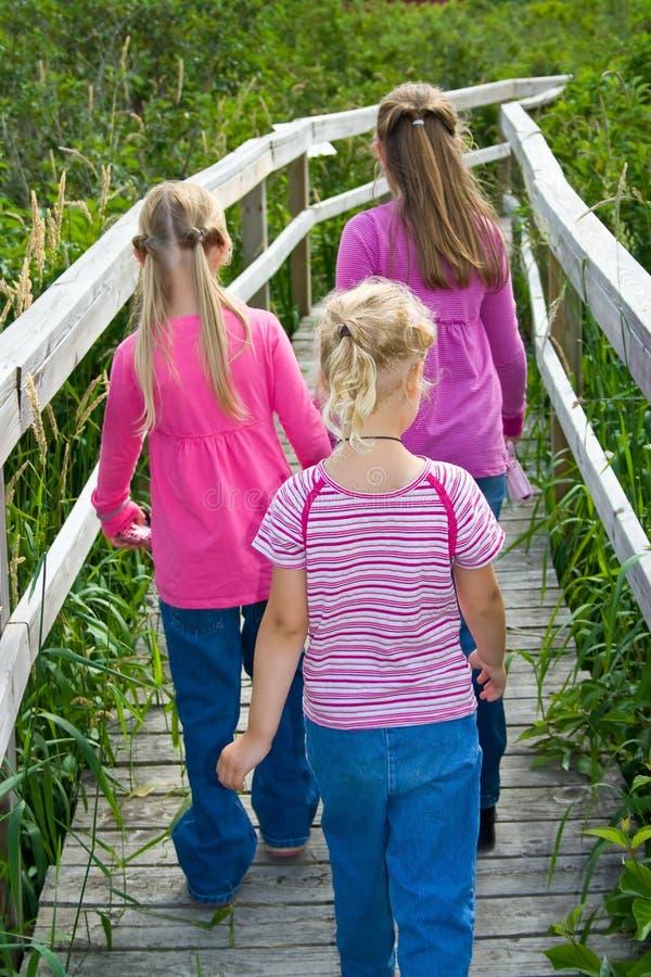 Três meninas que andam afastado em um passeio à beira mar. fotografia de stock
