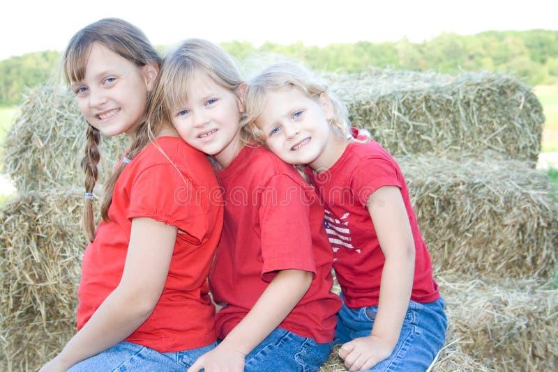 Três meninas que inclinam-se em se. imagens de stock