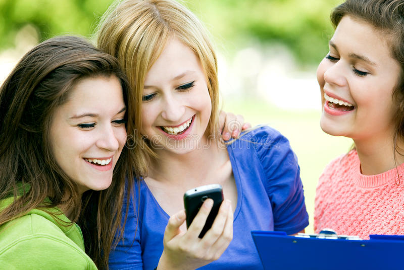 Três meninas que olham o telefone móvel imagem de stock