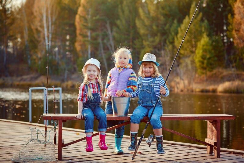 Três meninas que pescam, com varas de pesca e uma cubeta, em uma ponte de madeira em um dia morno do outono Estão amigáveis e fel fotografia de stock royalty free