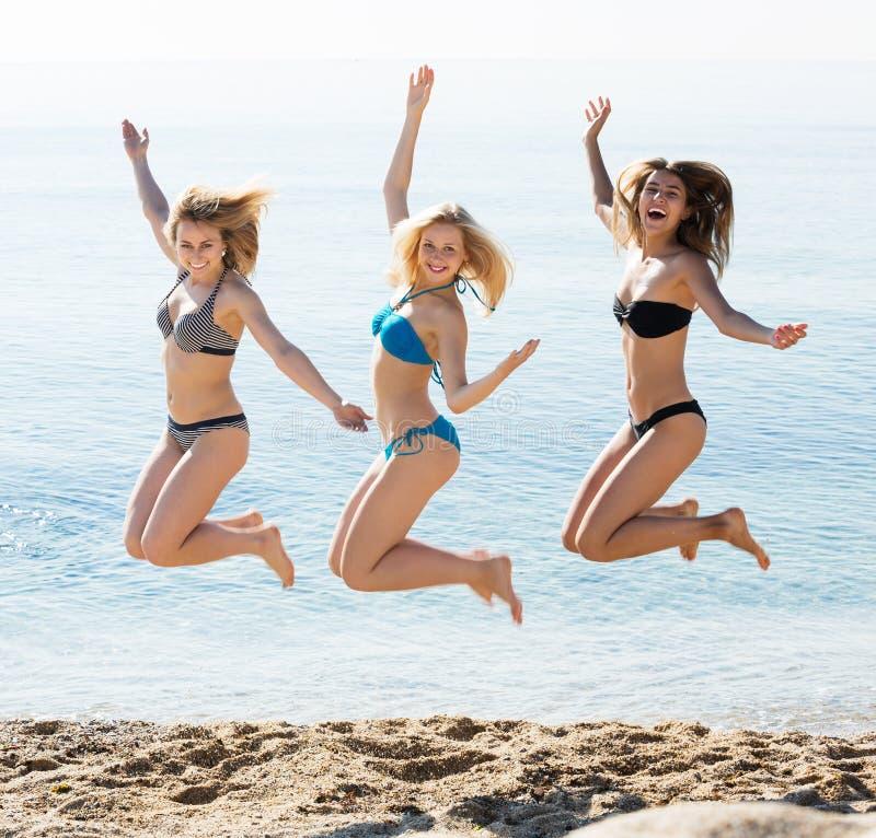 Três meninas que saltam na praia imagem de stock