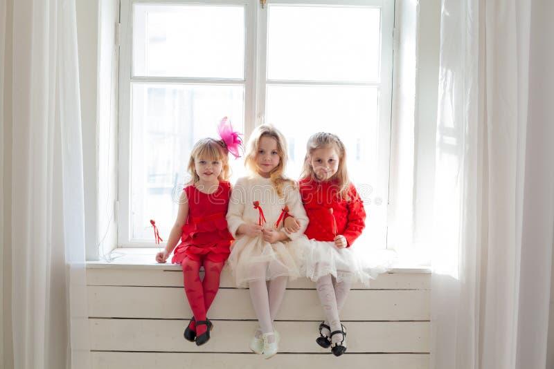 Três meninas que sentam-se com os balões vermelhos do coração imagens de stock royalty free