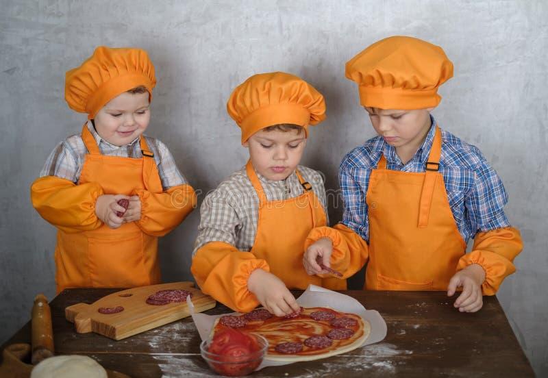 Três meninos europeus bonitos vestidos como cozinheiros são ocupados cozinhar a pizza três irmãos ajudam minha mãe a cozinhar a p foto de stock royalty free