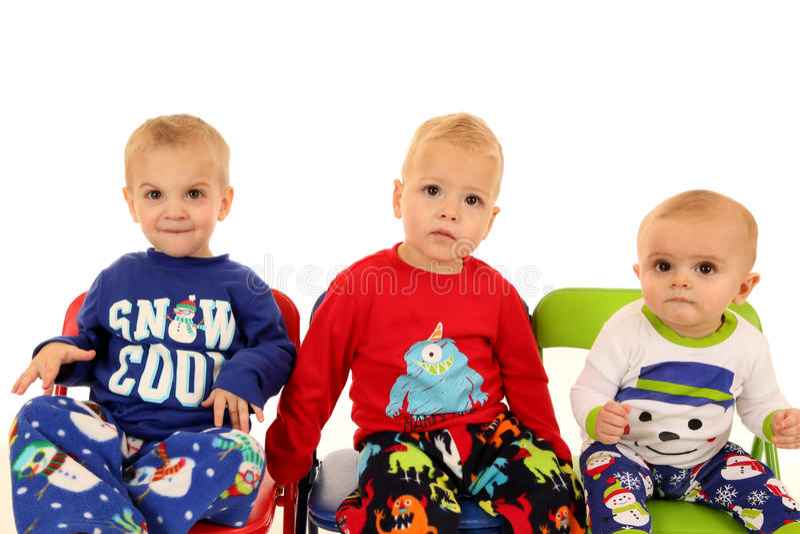 Três meninos novos bonitos que sentam pijamas vestindo do inverno imagens de stock royalty free