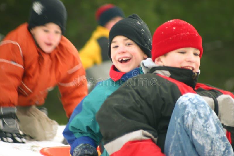 Três meninos Sledding imagem de stock