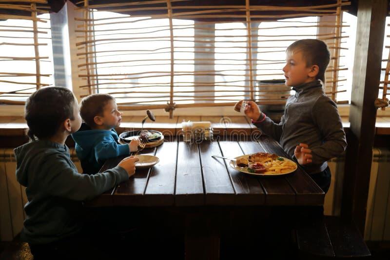 Três meninos têm o almoço foto de stock royalty free