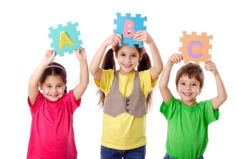 Três miúdos com letras fotos de stock