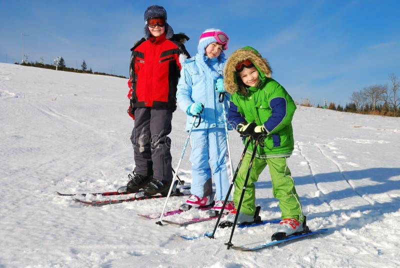 Três miúdos em esquis imagens de stock