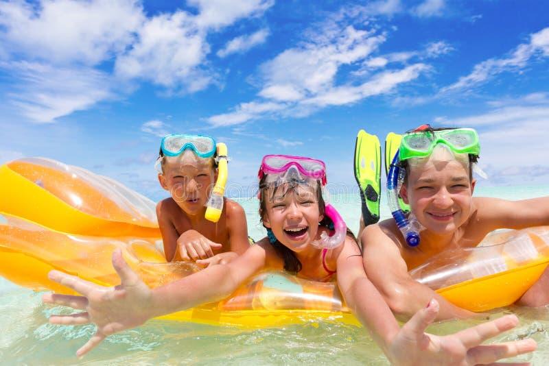 Três miúdos em uma jangada imagem de stock