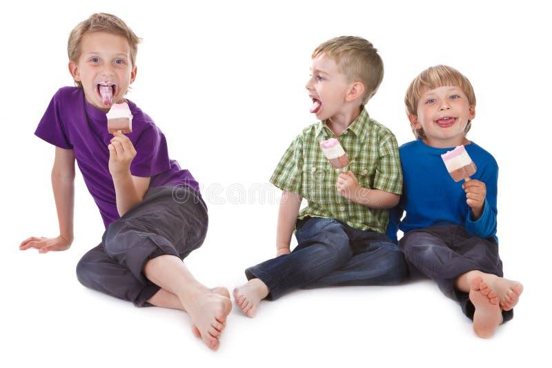 Três miúdos engraçados que comem o lolly de gelo fotografia de stock