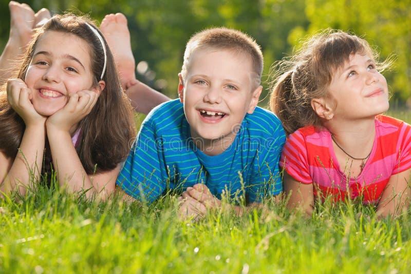 Três miúdos felizes na grama fotografia de stock royalty free