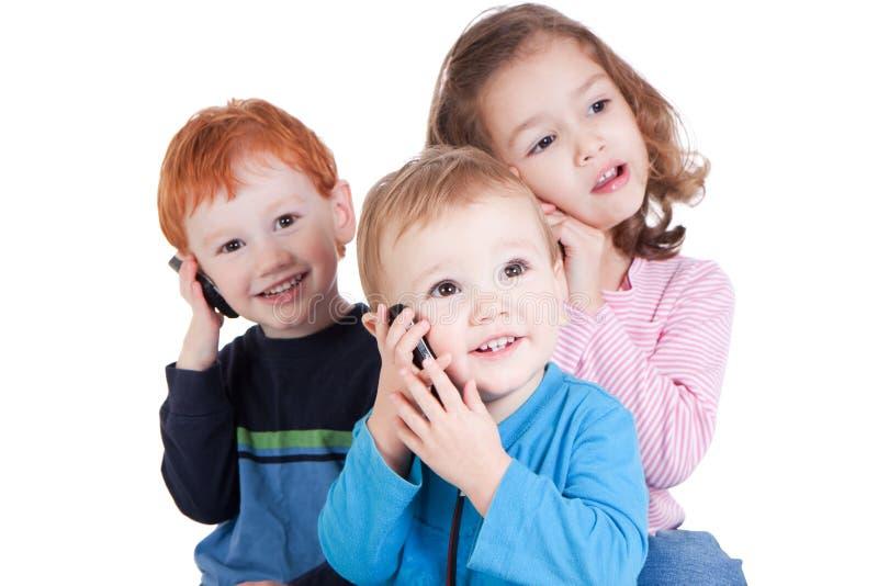 Três miúdos felizes que falam em telefones móveis imagens de stock royalty free