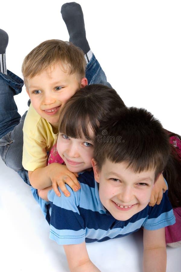 Três miúdos felizes que jogam no assoalho foto de stock