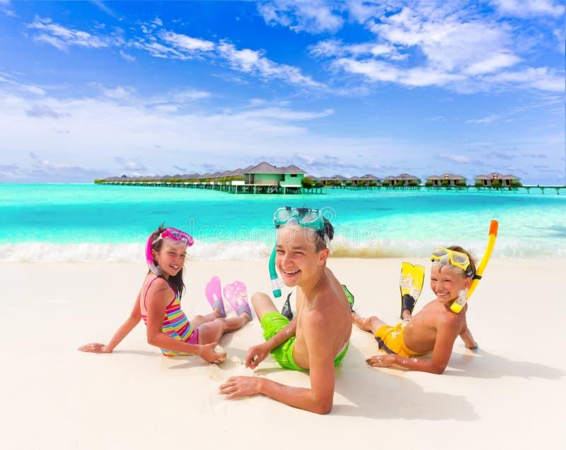 Três miúdos na praia imagem de stock