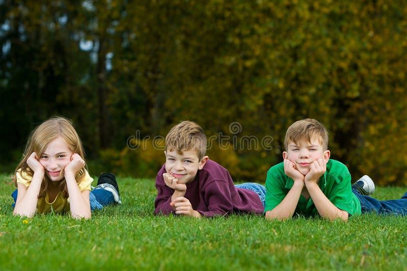 Três miúdos que coloc na grama fotos de stock royalty free