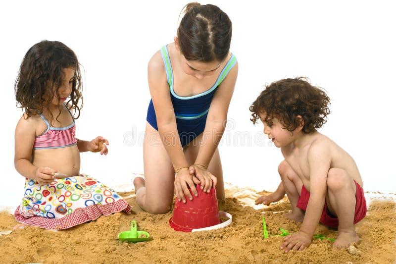 Três miúdos que jogam na areia imagem de stock royalty free