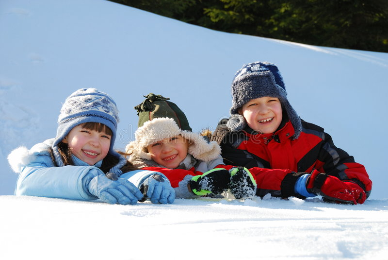 Três miúdos que jogam na neve imagem de stock