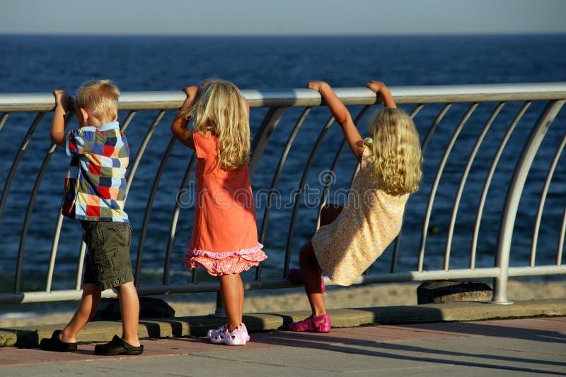 Três miúdos que olham para fora ao mar imagens de stock royalty free