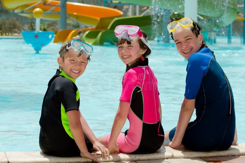 Três miúdos que sentam o poolside imagem de stock