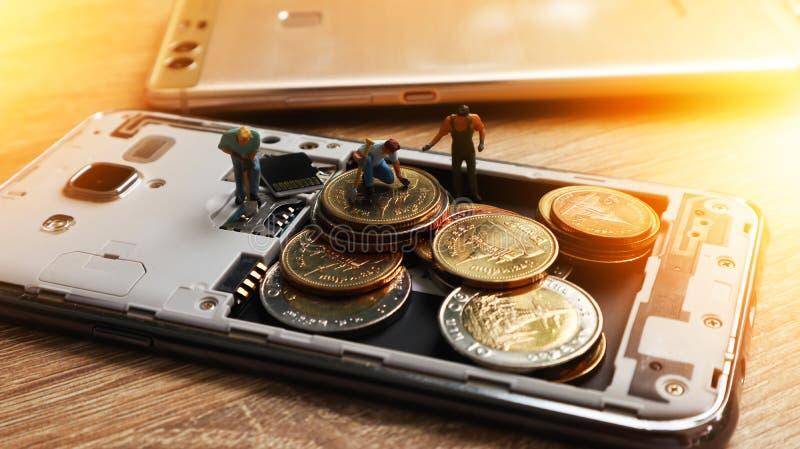 Três mini figuras diminutas com mantêm o dinheiro no móbil Cashles fotos de stock