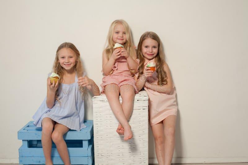 Três moças bonitas e pirulitos doces dos doces fotos de stock