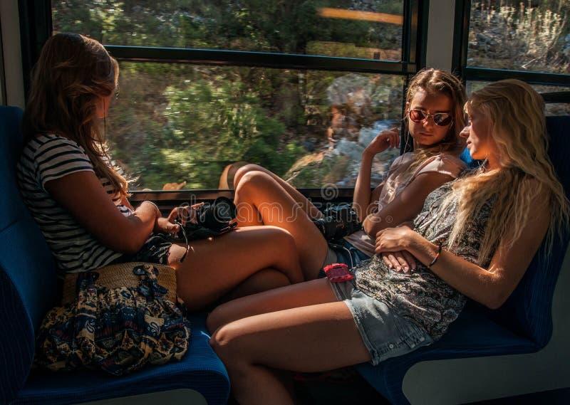 Três moças na iluminação do por do sol que viajam no carro de trem e nas suas reflexões na janela imagens de stock royalty free