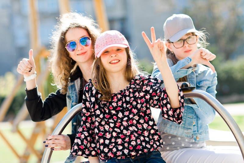 Três moças no campo de jogos que senta-se no carrossel pequeno - a vitória, bate acima e para bater para baixo foto de stock