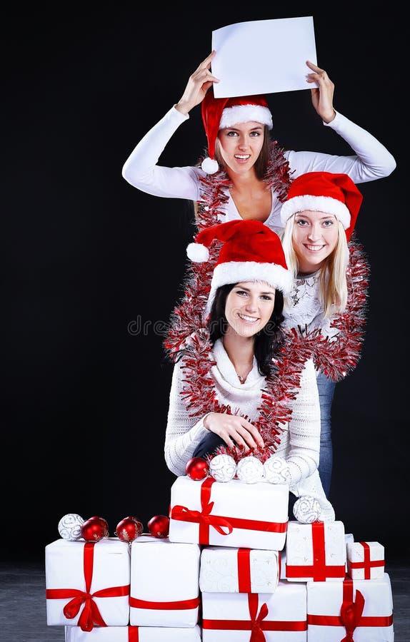 Três moças no traje de Santa Claus que mostra a folha vazia fotografia de stock