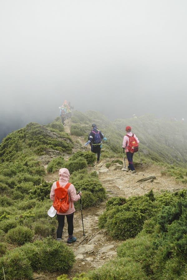 Três moças que andam junto e que falam sobre algo na fuga da montanha de Hehuan Ainda têm o uma grande distância a percorrer fotografia de stock royalty free