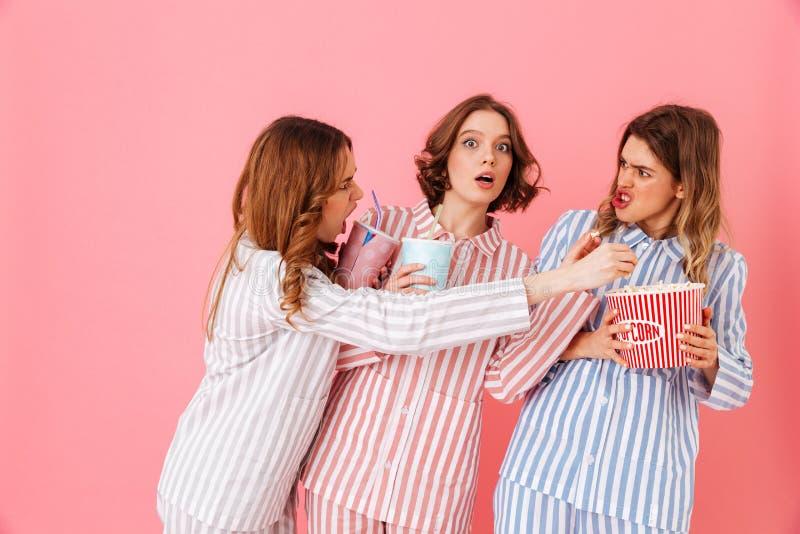 Três moças 20s no durin colorido do milho de PNF comer do homewear fotografia de stock