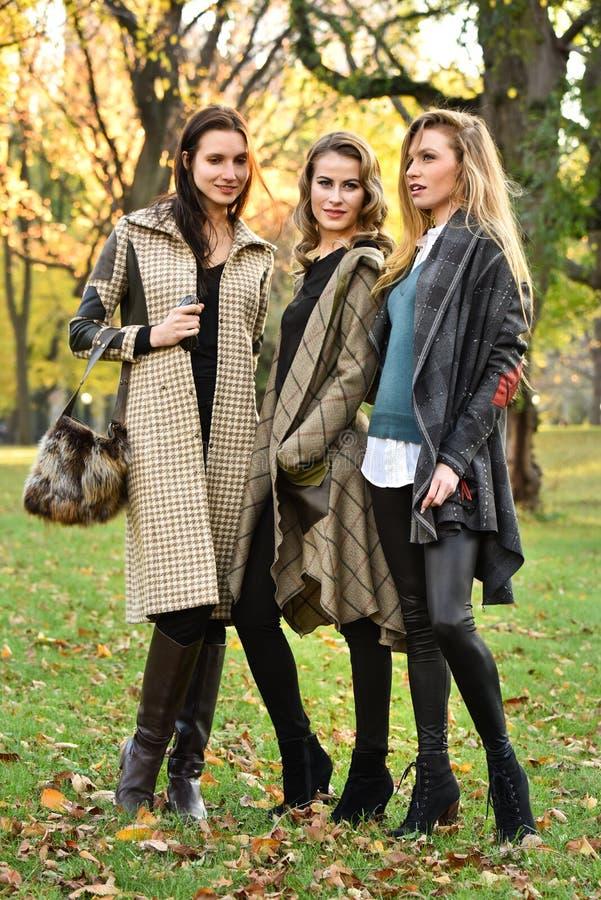 Três modelos novos bonitos na roupa elegante do outono que levanta no Central Park fotos de stock royalty free