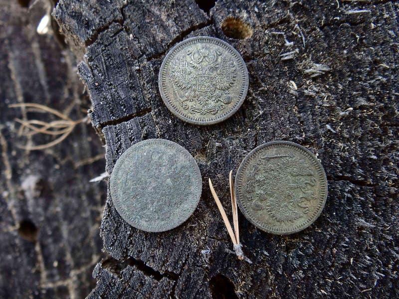 Três moedas de prata na madeira cinzenta no ar livre imagem de stock