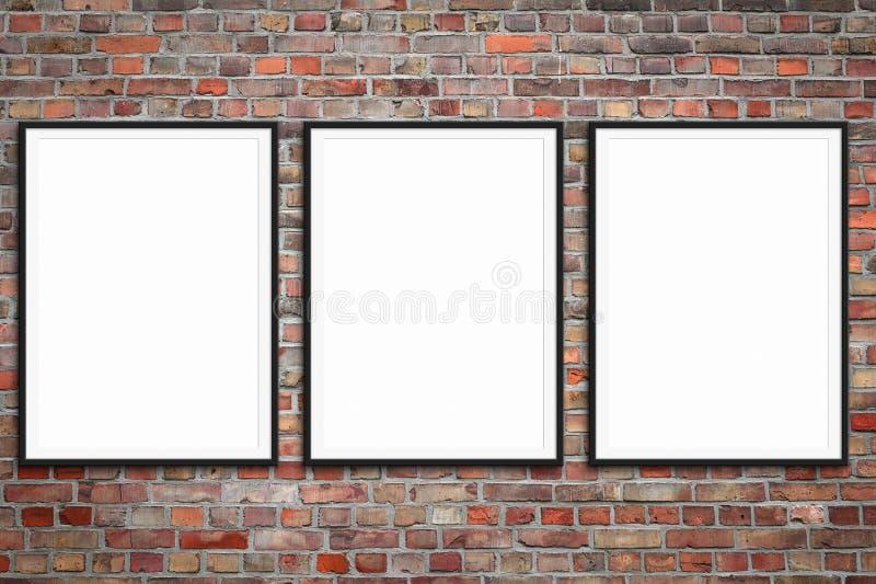 Três molduras para retrato vazias na parede de tijolo - modelo quadro do cartaz com fundo da parede de pedra imagens de stock royalty free