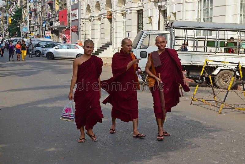 Três monges budistas que andam abaixo de uma rua em Yangon, Myanmar imagens de stock