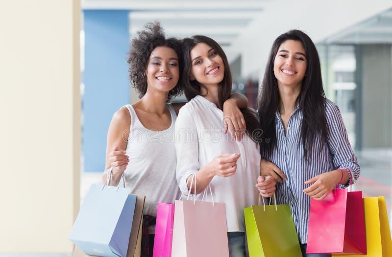 Três mulheres bonitas com sacos coloridos que andam na alameda imagens de stock