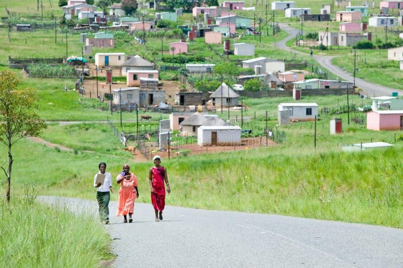 Três mulheres com as casas de Mandela no fundo de Zulu Village, Zululândia, África do Sul foto de stock royalty free