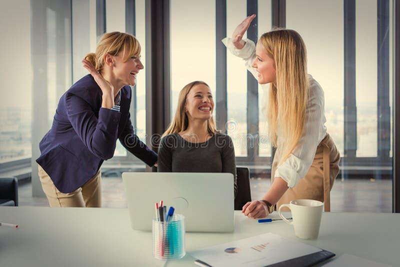 Três mulheres de negócio no escritório moderno que comemoram o bom projeto resultam imagem de stock