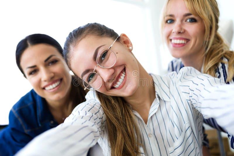 Três mulheres de negócio novas bonitas que tomam um selfie com telefone celular na oficina costurando imagens de stock