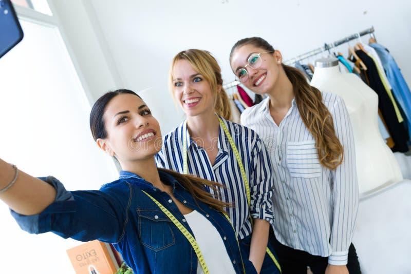 Três mulheres de negócio novas bonitas que tomam um selfie com telefone celular na oficina costurando fotografia de stock