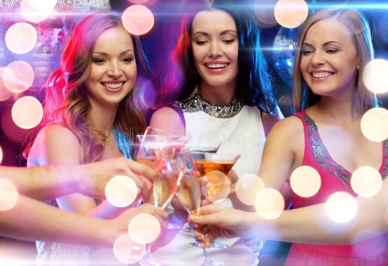 Três mulheres de sorriso com os cocktail no clube foto de stock
