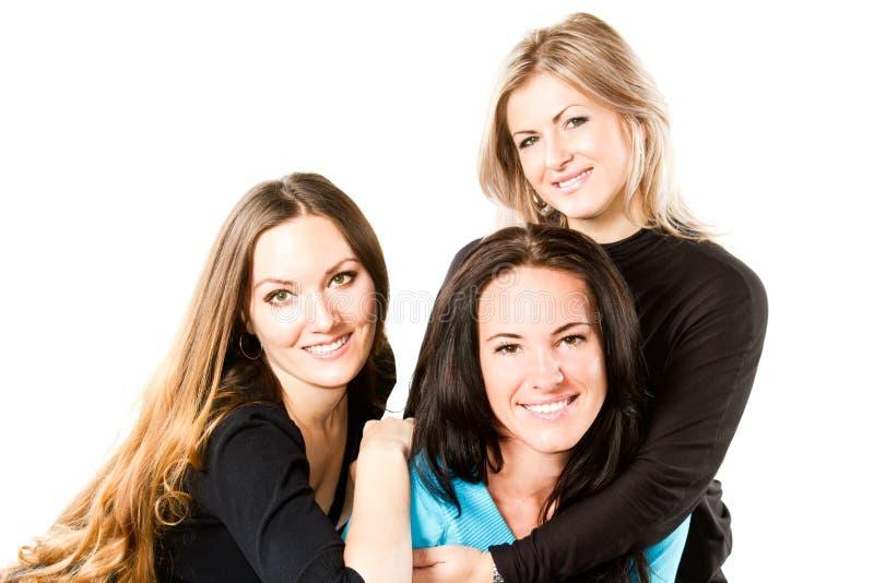três mulheres de sorriso novas atrativas fotografia de stock